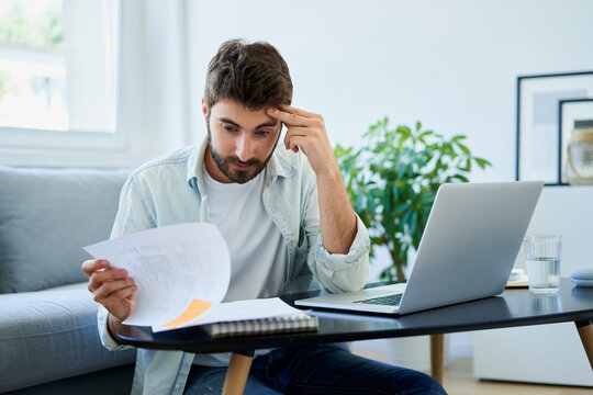 Worried young man looking on bills while at home