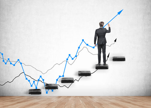 Businessman is staying on ladder and painting blue graph