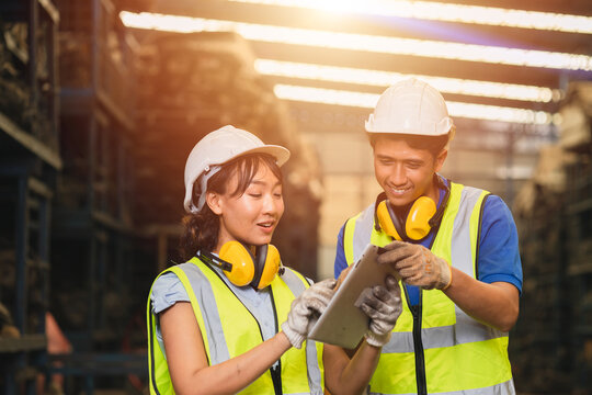 Asian young man and women worker team engineer working help support together using tablet happy smile to work in factory industry