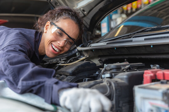 Woman worker at automobile service center, Female in auto mechanic work in garage car technician service check and repair customer car, inspecting car under hood battery engine oil change