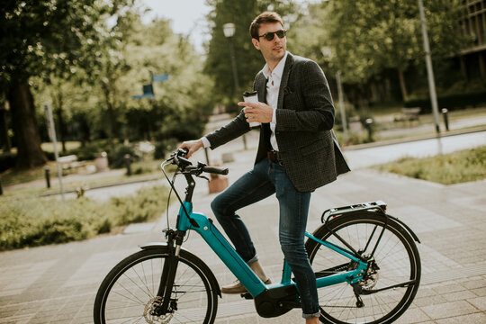 Young businessman on the ebike with takeaway coffee cup