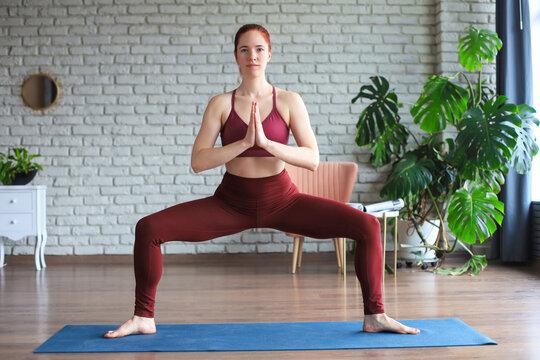 Sporty woman practicing yoga, doing Garland exercise, Malasana pose, working out, wearing sportswear, in yoga studio.