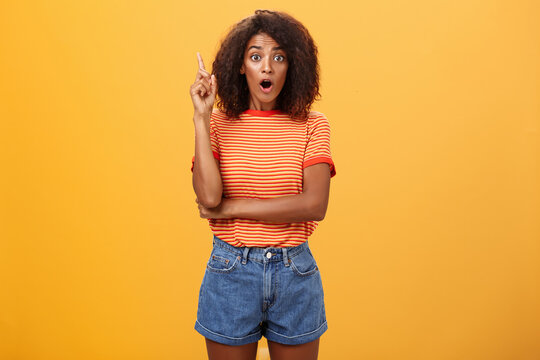 Girl finally understood riddle adding suggestion outloud. Excited thrilled good-looking dark-skinned woman staring amazed raising index finger in eureka gesture having idea over orange wall