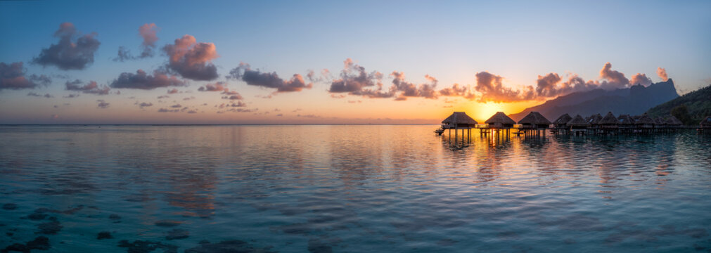 Overwater bungalows at a luxury beach resort at sunset