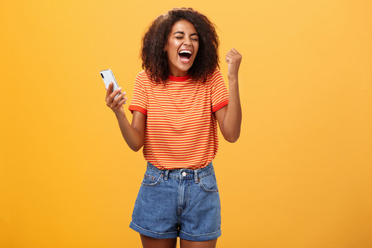 Portrait of ambitious happy young african american girl yelling from happiness and triumph clenching fist in joy and celebration feeling excited and relieved holding smartphone over orange wall