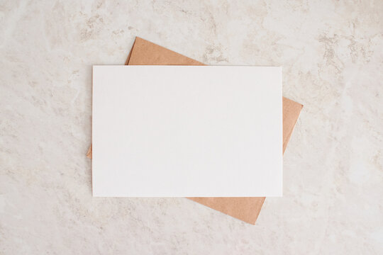 Blank card mock up. Layout of sheet of paper on craft envelope and marble texture. Horizontal canvas template for greeting, wedding cards, invitations. Natural beige colors.