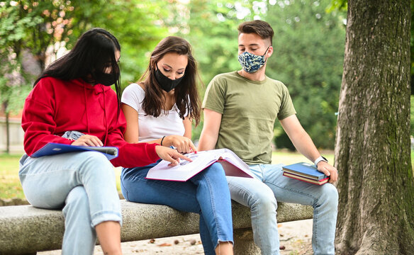 Three students studying together sitting on a bench outdoor and wearing masks during coronavirus times