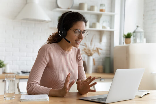 Confident tutor. Smart latin female in glasses sit by laptop at home office provide video lesson explain new material. Young lady expert interpreter in modern headset work online give teleconsultation