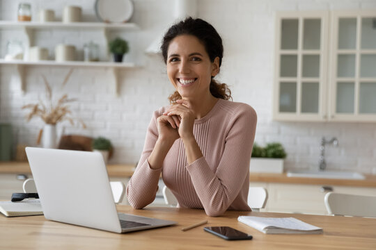 Remote worker portrait. Smiling hispanic woman employee student sit by desk before pc enjoy distant job learning. Confident young lady freelancer work from home look at camera pose at domestic office