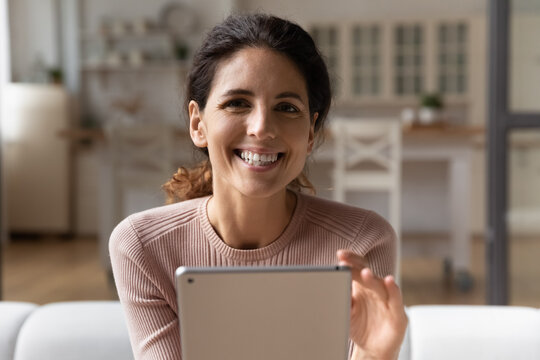 Easy online learning. Headshot portrait of motivated latin woman study in internet from home sit on cozy sofa hold digital pad look at camera above screen. Happy young lady relax using modern tablet