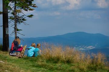 Fototapeta Rodzina i przyjaciele na letniej wyprawie w góry w ciepły, słoneczny dzień