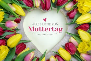 Alles liebe zum Muttertag. Herz aus Holz umgeben von Blumen (Tulpen) mit Glückwunsch.