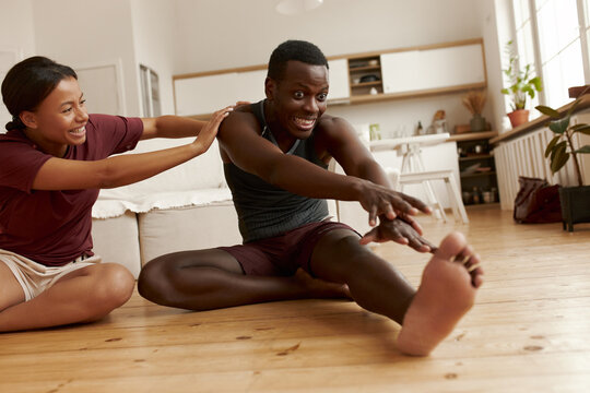 Indoor image of beautiful young Latin female laughing while sitting on floor pushing her funny inflexible black boyfriend who is doing forward bend. People, relationships and active lifestyle