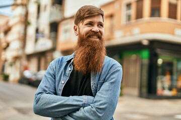 Fototapeta Young irish hipster man smiling happy with arms crossed at the city.