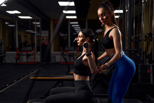 Beautiful athlete woman exercising with dumbells in fitness club.