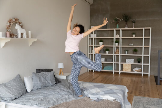 Overjoyed active young latin lady having fun in bedroom jump on firm comfortable mattress. Funny teen female dance on bed enjoy good happy life excited with new flat modern renovated interior design