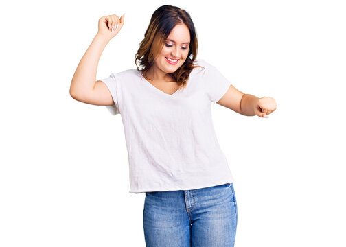 Young beautiful caucasian woman wearing casual white tshirt dancing happy and cheerful, smiling moving casual and confident listening to music