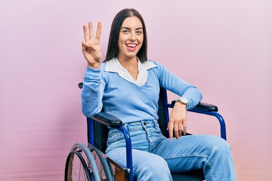 Beautiful woman with blue eyes sitting on wheelchair showing and pointing up with fingers number three while smiling confident and happy.
