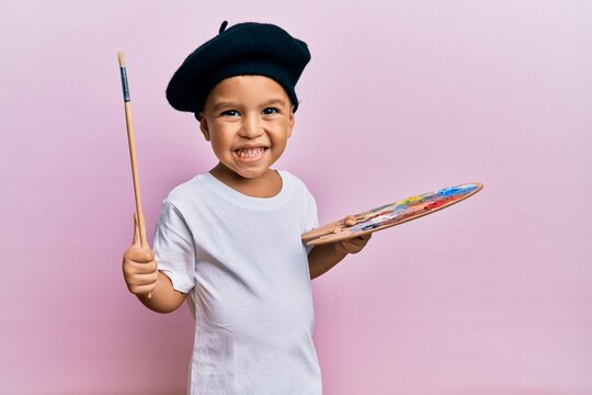 Adorable latin toddler smiling happy wearing artist style using paintbrush and palette over isolated pink background.