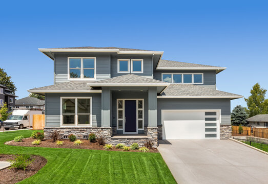 Exterior of new home on bright sunny day with blue sky. Features two car garage, front yard with green grass, and modern design