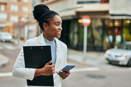 Young african american businesswoman using smartphone holding clipboard at the city.
