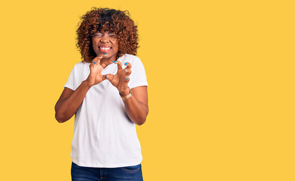Young african american woman wearing casual white tshirt disgusted expression, displeased and fearful doing disgust face because aversion reaction. with hands raised