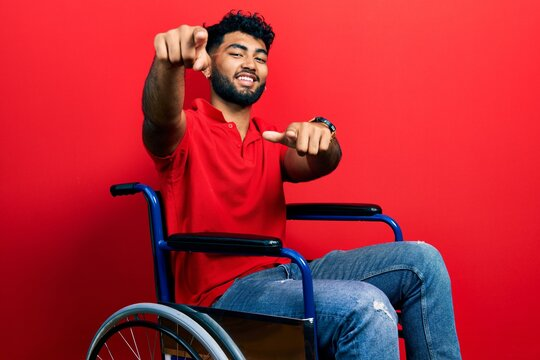 Arab man with beard sitting on wheelchair pointing to you and the camera with fingers, smiling positive and cheerful