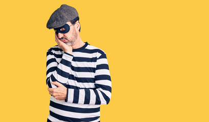 Middle age handsome man wearing burglar mask thinking looking tired and bored with depression problems with crossed arms. - fototapety na wymiar