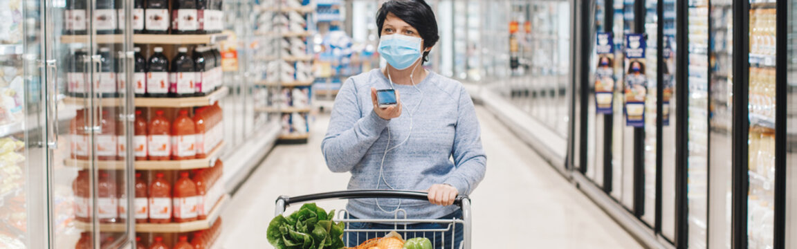 Middle age brunette woman shopping in grocery store supermarket and talking on audio chat  cell phone. New social media chat app. Speaker in live stream on smartphone. Using technology.