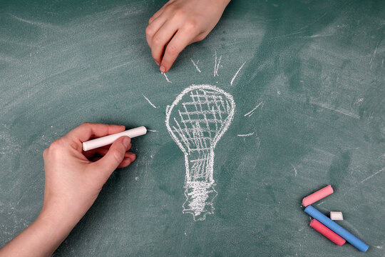 Brainstorming, Start-Up and Marketing Plan concept. Woman's and a child's hand draws on a chalkboard light bulb