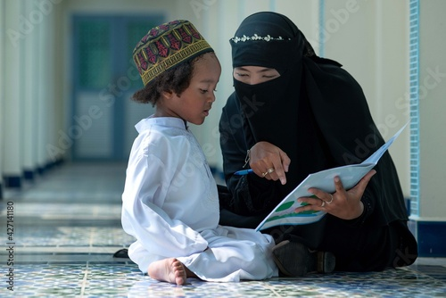 Muslim mother teaches her son to read Arabic, relationship between Muslim mother and child, Mother's day