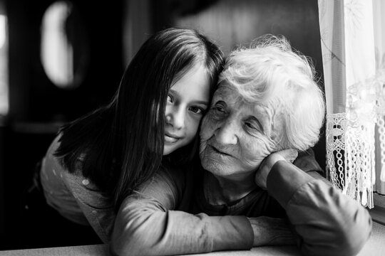 Little girl hugs her old grandmother. Black and white photo.
