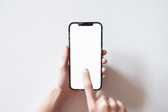 Bangkok, Thailand - Apr 10, 2021: Close up hand holding black smartphone iPhone 12 Pro Max with white screen. Isolated on white background. Mobile phone frameless design concept.