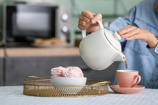 Woman pouring aromatic tea from teapot into cup in kitchen
