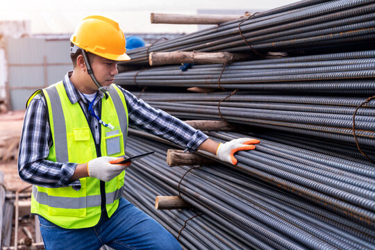 Construction engineer or worker use a tablet checking quality steel for concrete foundation and check the quality of round bar at construction site