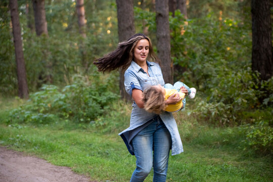 young mother is spinning with a baby in her arms. happy mom dancing with toddler on the background of nature and forest. mom and daughter laugh