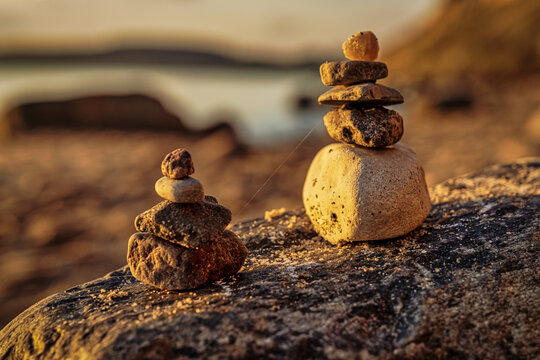 A cairn on a beach with sand in the blurry background