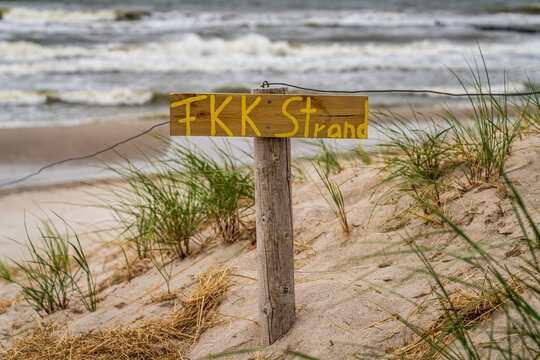 Sign: FKK Strand (German for 'naturist beach'), with dunes and sand in the background