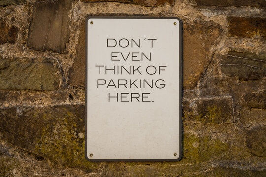 Sign: Don't even think of parking here - seen on a brickwall
