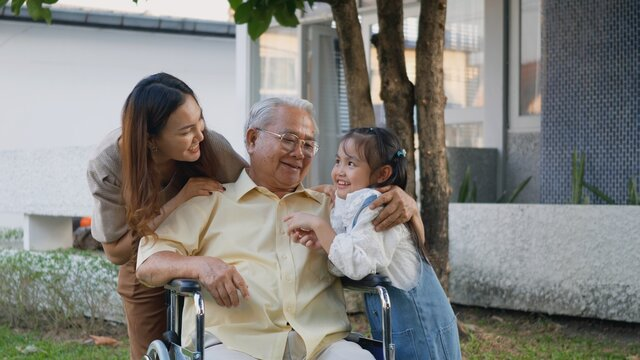 Disabled senior grandpa on wheelchair with grandchild and mother in park, Happy Asian three generation family having fun together outdoors backyard, Grandpa and little child smiling and laughed