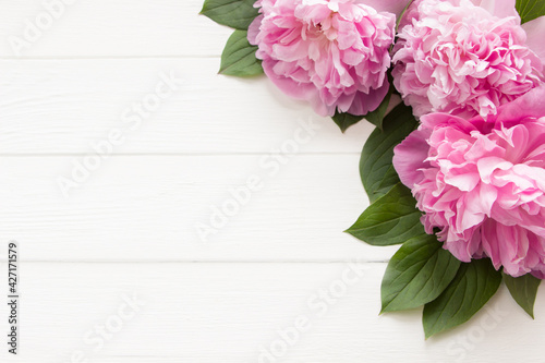 Pink peony flowers  on white wooden background with copy space. Mother's day, 8 march, women's day or wedding concept. Spring flowers background