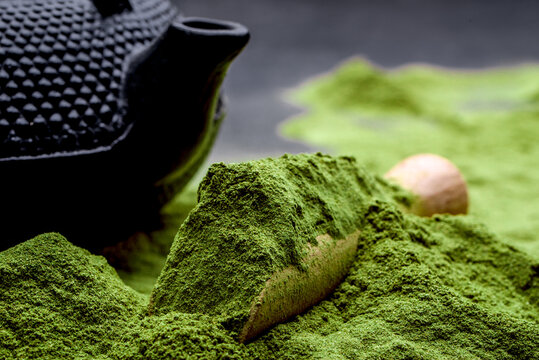 Powdered green tea and set for matcha on black background