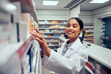 Wall Murals Smiling young female pharmacist wearing labcoat standing behind counter looking for medicine in shelf