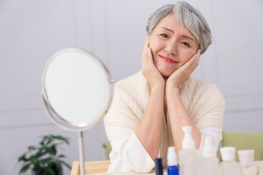 Close-up photo of a gray-haired elderly woman,skin care and make up