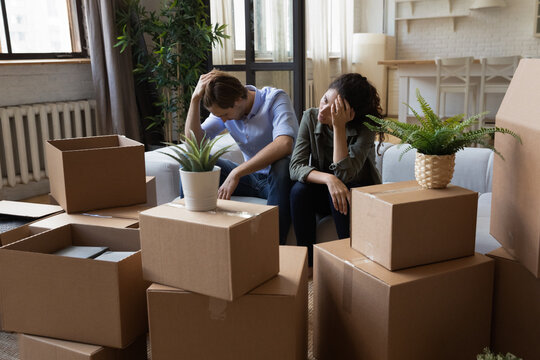 Unhappy frustrated couple sitting on couch with cardboard boxes, eviction, family having problem with dwelling, money or mortgage, worried woman and man lost home, bankruptcy or debt concept