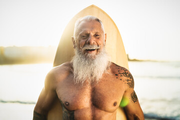 Happy Senior male having fun surfing during sunset time - Retired man training with surfboard on the beach - Elderly healthy people lifestyle and extreme sport concept