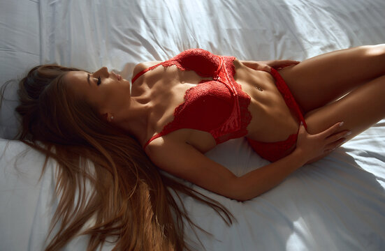 Top closeup view of sexy young gorgeous woman with perfect fit body lying on bed. Caucasian female model with athletic body wearing red lace lingerie enjoying sunny morning, slowly taking off pants.