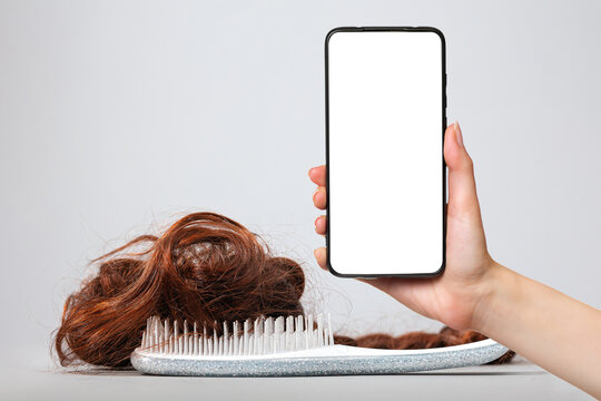 A white comb with false hair. White background. A female's hand holds a smartphone with a white screen. Mock up. The concept of buying and selling hair