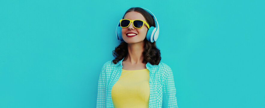 Portrait close up of smiling young woman with headphones listening to music on a blue background