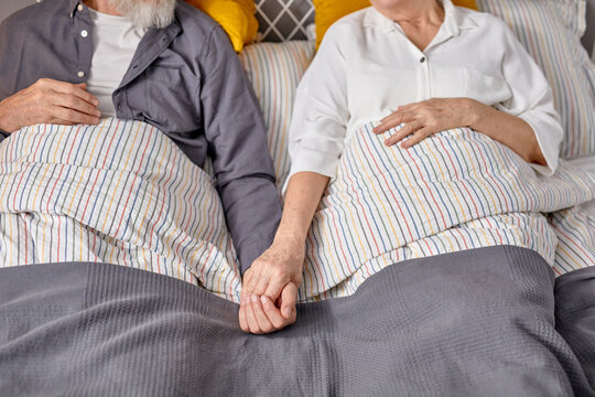 top view on cropped senior couple lying on bed holding hands of each other